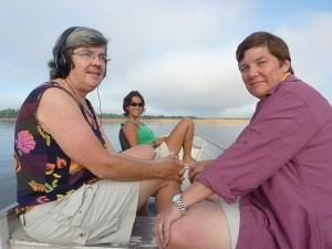 Camila Ferrara (INPA) shares headphones with Tiaro Landcare members (Marilyn & Debbie) so they can  listen to wild turtles communicate - Rio Trombetas, Amazona